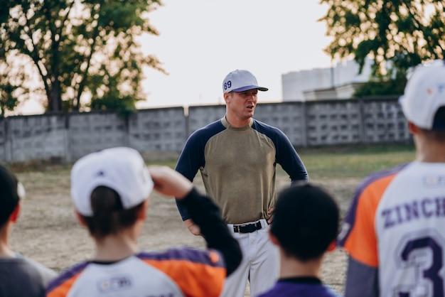 Um treinador sério se comunica com seus alunos ao ar livre Foto Premium