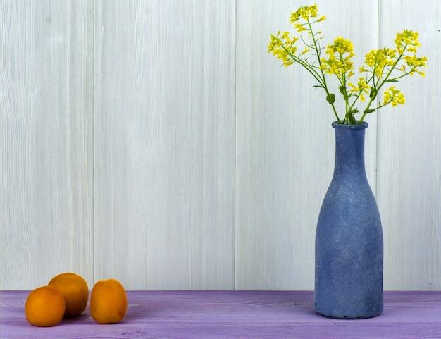 Um vaso azul com um campo de flores e de abricós amarelos na tabela. Foto Premium