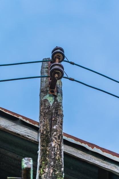 Um velho poste elétrico de madeira com céu azul Foto Premium