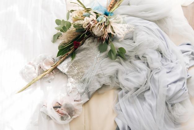 Um vestido de noiva deslumbrante e delicado, com miçangas e rendas, fica ao lado de um buquê de proteus. manhã da noiva Foto Premium