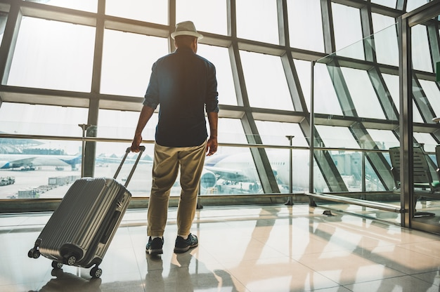 Um viajante masculino usando um chapéu cinza preparando-se para viajar Foto Premium