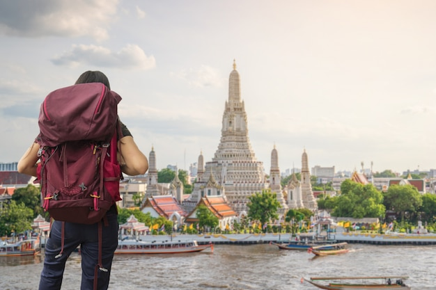 Um viajante que viaja no templo de wat arun ratchawararam ratchawaramahawihan em banguecoque, tailândia Foto Premium
