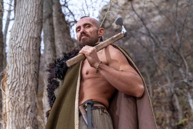 Um viking barbudo está entre as árvores vestido com a pele de um animal e segura um machado de batalha na mão Foto Premium