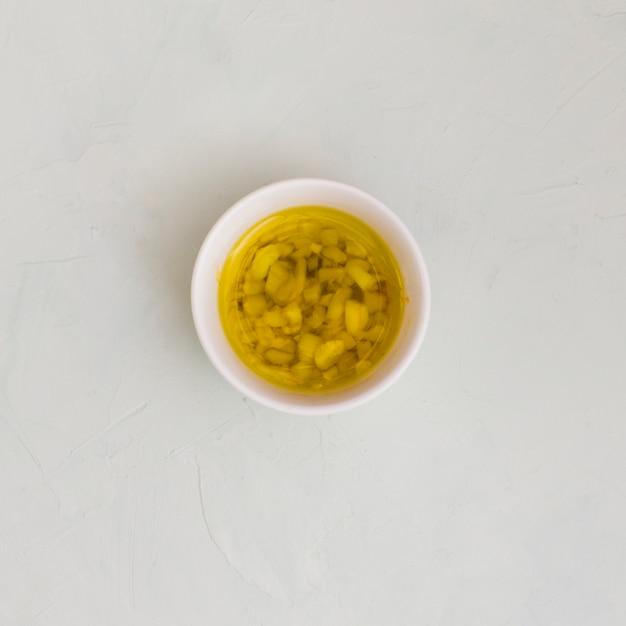 Um, visão aérea, de, alho, infundido, azeite oliva, em, tigela, branco, textured, fundo Foto gratuita