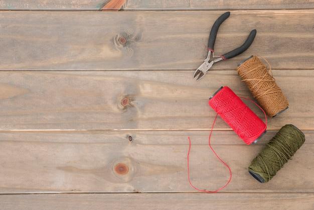 Um, visão aérea, de, alicates, e, coloridos, fios, carretéis, ligado, escrivaninha madeira Foto gratuita