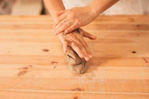 Um, visão aérea, de, femininas, mãos, sobre, amassado, barro, ligado, tabela madeira Foto gratuita