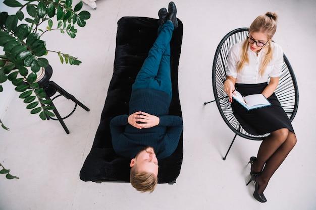 Um, visão aérea, de, jovem, femininas, psicólogo, consultar, homem jovem, durante, psicológico, terapia, sessão Foto gratuita