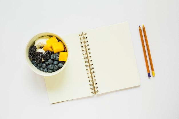 Um, visão aérea, de, lápis, e, em branco, caderno espiral, com, saudável, frutas, em, copo Foto gratuita