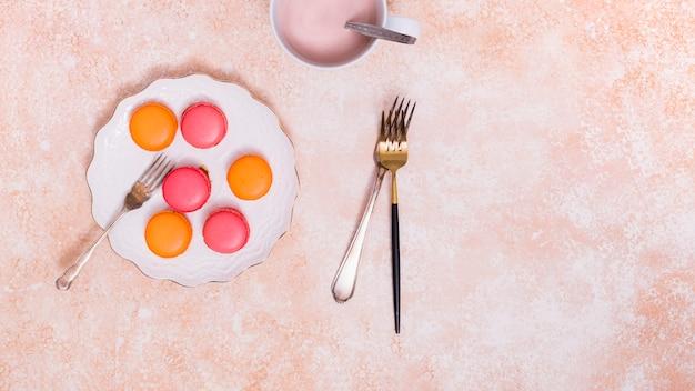 Um, visão aérea, de, macaroons, ligado, branca, prato cerâmico, com, garfos, sobre, a, textured, fundo Foto gratuita