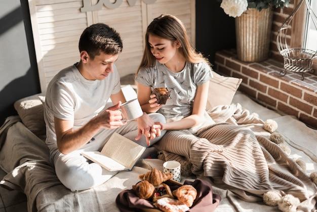 Um, visão aérea, de, par, sentar-se cama, segurando, xícara café, e, muffin, em, mão Foto gratuita