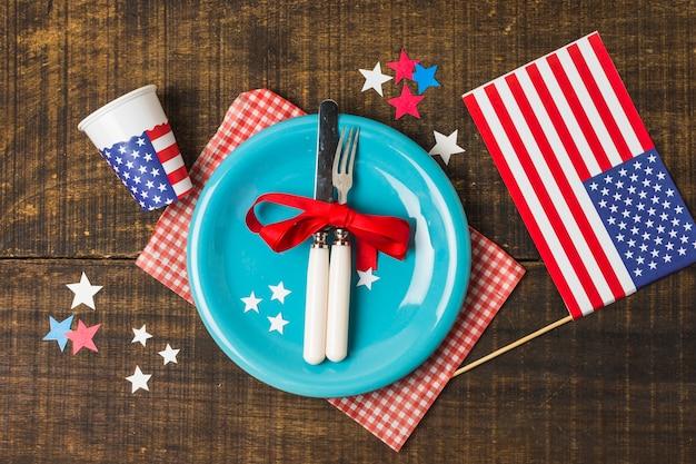 Um, visão aérea, de, prato azul, e, cutelaria, com, bandeira eua, e, vidro descartável, ligado, tabela madeira Foto gratuita
