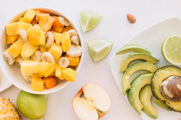 Um, visão aérea, de, salada fruta, tigela, e, fatias abacate, branco, fundo Foto gratuita