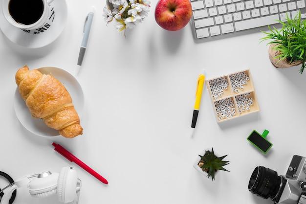 Um, visão aérea, de, um, escritório, stationeries, com, croissant assado, e, maçã, branco, escrivaninha Foto gratuita