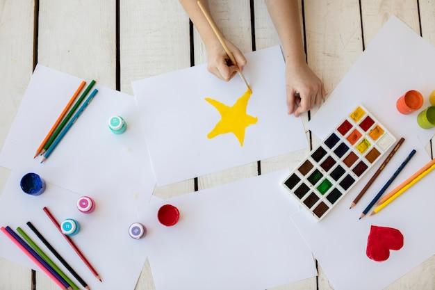 Um, visão aérea, de, um, menina, quadro, a, amarela, estrela, com, pincel, branco, papel Foto gratuita