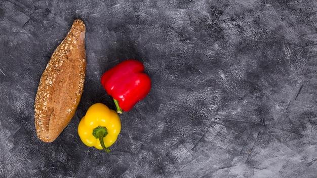Um, visão aérea, de, vermelho amarelo, pimentas sino, com, pão, contra, pretas, textured, fundo Foto gratuita