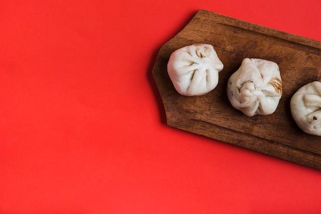 Um, visão aérea, dumplings, ligado, madeira, bandeja, contra, vermelho, fundo Foto gratuita