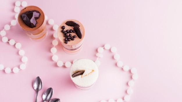Um, visão geral, de, mergulhado, sobremesas, com, decoração, ligado, cor-de-rosa, fundo, com, colar, e, colheres Foto gratuita
