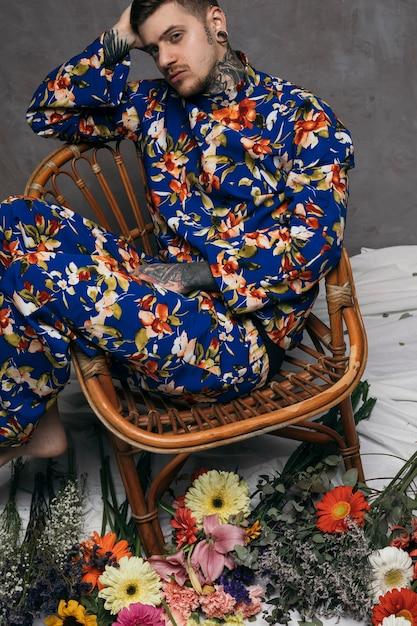 Um, vista aérea, de, relaxado, homem jovem, sentar-se cadeira, com, flores coloridas Foto gratuita
