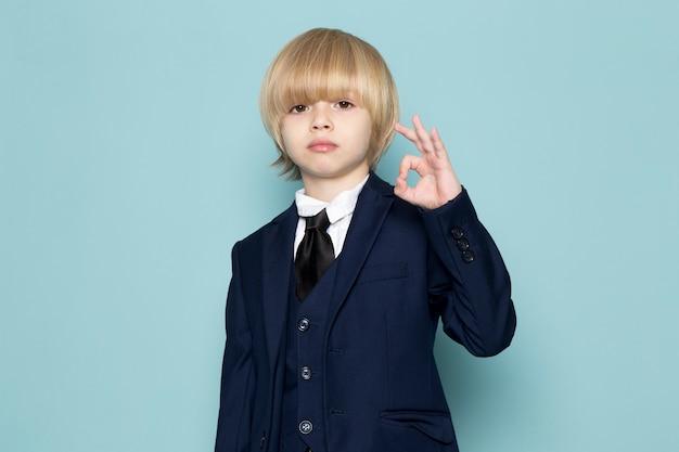 Um, vista dianteira, cute, menino negócio, em, azul, clássico, paleto, posar, mostrando, tudo bem, sinal Foto gratuita