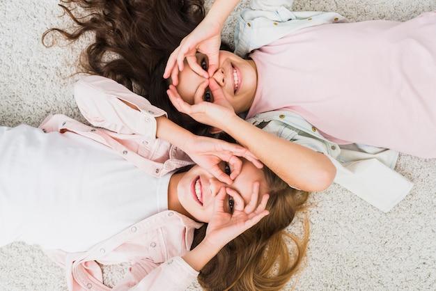 Um, vista elevada, de, um, meninas, mentindo, ligado, tapete, fazendo, ok, gesto, semelhante, binocular Foto gratuita