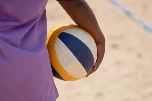 Um, voleibol praia, atleta segurando, voleibol praia, em, mão Foto Premium