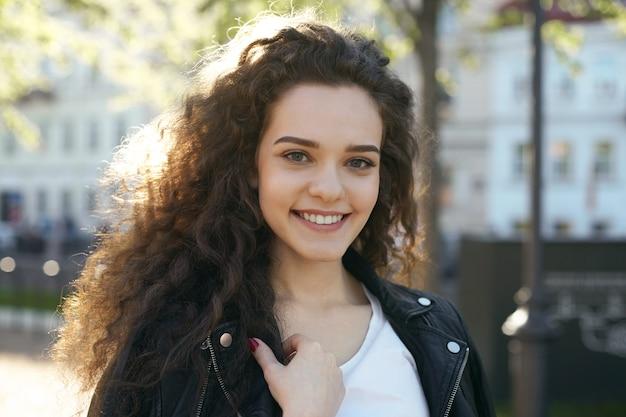 Uma adolescente com um penteado ondulado posando Foto gratuita