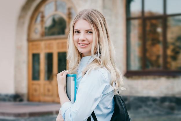 Uma aluna loira está sorrindo e segurando uma pasta e um caderno nas mãos dela sobre um fundo universitário Foto Premium
