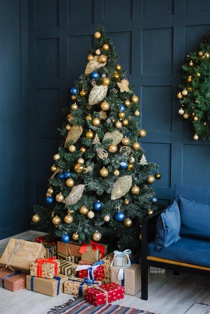 Uma árvore de natal com balões azuis e dourados com presentes embaixo fica na sala de estar com paredes azuis Foto Premium