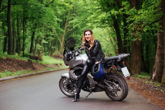 Uma atraente garota sexy vestida de couro posando perto de uma moto esportiva do lado de fora Foto gratuita