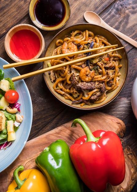 Uma bacia da vista aérea de carne de vaca deliciosa tailandesa; camarão com macarrão udon e molhos Foto gratuita