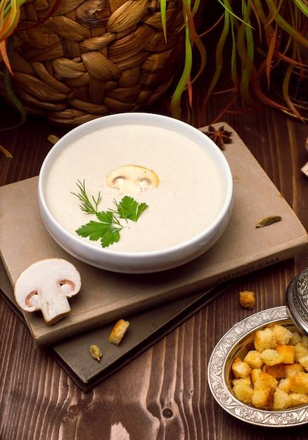 Uma bacia de creme caseiro delicioso da sopa de cogumelo com pão roasted. Foto gratuita