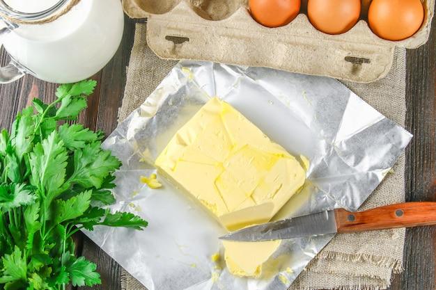 Uma barra de manteiga é cortada em pedaços em uma placa de madeira com uma faca Foto Premium