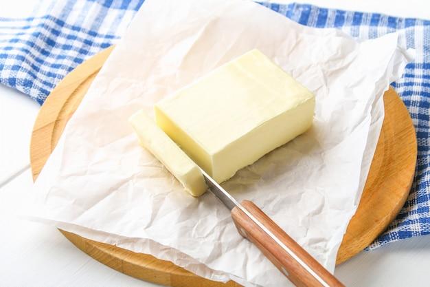 Uma barra de manteiga em uma placa de madeira com uma faca, sobre uma mesa branca. ingredientes para cozinhar Foto Premium