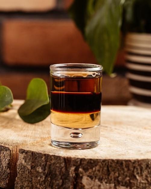 Uma bebida alcoólica de vista frontal dentro de um copo na mesa de madeira marrom Foto gratuita