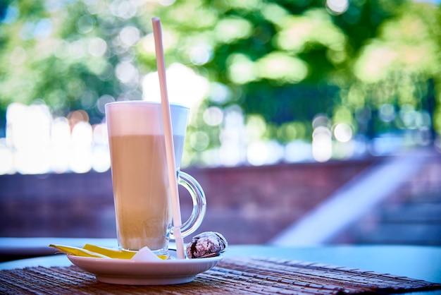 Uma bebida de café em um copo em um pires com biscoitos Foto Premium
