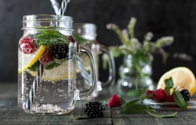 Uma bebida refrescante de limão em um copo de vidro sobre uma mesa de madeira Foto Premium