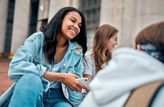 Uma bela aluna afro-americana se senta com amigos nos degraus perto do campus e se comunica. Foto Premium