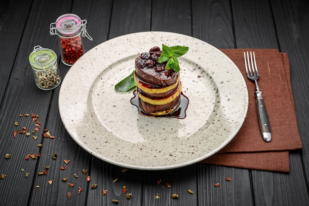Uma bela apresentação de carne frita com maçã, alecrim e molho de cereja Foto Premium