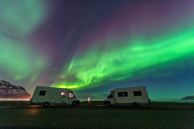 Uma bela aurora verde e vermelha dançando sobre a lagoa de jokulsarlon, islândia Foto Premium