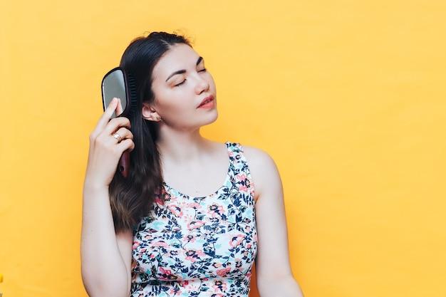 Uma bela jovem de vestido penteia seu cabelo escuro com pente Foto Premium