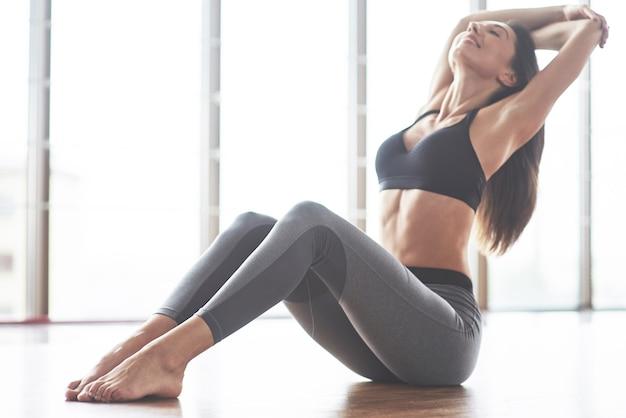 Uma bela mulher de ioga praticando em um amplo ginásio leve. Foto gratuita