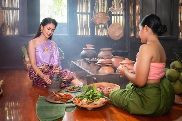 Uma bela mulher tailandesa e ela usa trajes tradicionais tailandeses, ambos mestres e servos. eles estão sentados e cozinhando na cozinha. conceito de vida no passado do povo ayutthaya Foto Premium