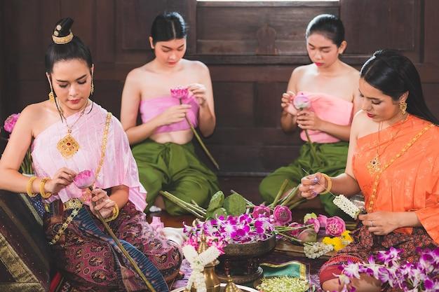 Uma bela mulher tailandesa e ela usa trajes tradicionais tailandeses, ambos mestres e servos. eles estão sentados preparando flores em uma casa de madeira para fazer mérito no dia do buda. Foto Premium