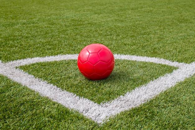 Uma bola de futebol vermelha fica no canto do campo de futebol ao lado da linha Foto Premium