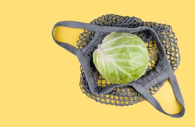 Uma cabeça de repolho encontra-se em um saco de barbante ecológico em um amarelo Foto Premium