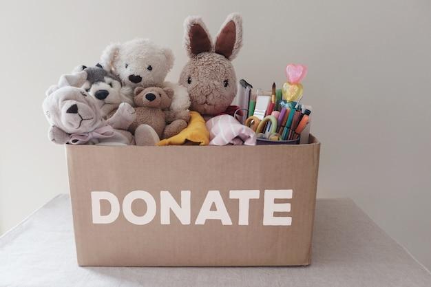 Uma caixa cheia de brinquedos usados, panos, livros e papelaria para doação Foto Premium