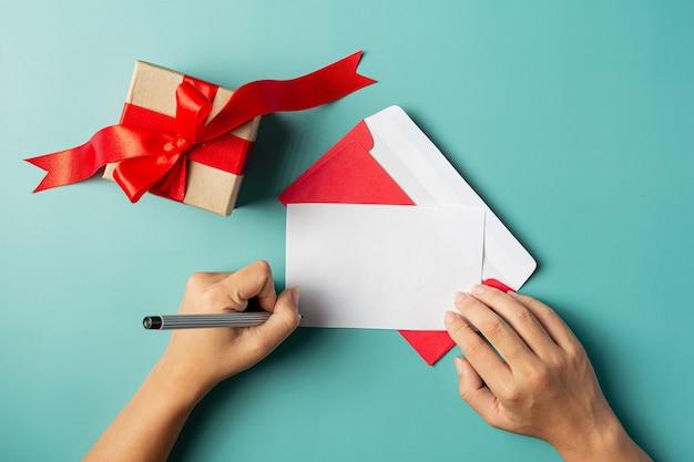 Uma caixa de presente colocada ao lado da mão de uma mulher está escrevendo um cartão de felicitações Foto gratuita