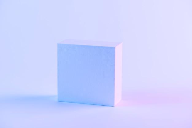 Uma caixa fechada em branco contra um fundo roxo Foto gratuita