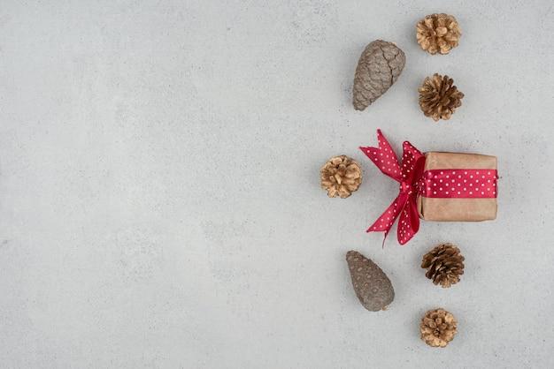 Uma caixinha de presente com laço vermelho e muitas pinhas no fundo branco Foto gratuita