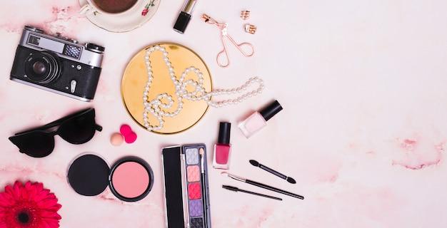 Uma câmera antiga vintage; oculos escuros; flor gerbera; esponja; colar; e produtos cosméticos no pano de fundo rosa Foto gratuita